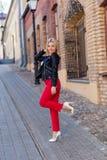 Porträt einer schönen Blondine in den roten Hosen Stockfotografie