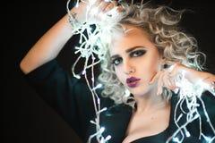 Porträt einer schönen Blondine mit einer Girlande Stockfotos