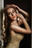 Porträt einer schönen braunhaarigen Frau in einem Goldkleid und -krone stockbilder