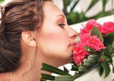 Porträt einer schönen Braut, die rote Blumen schnüffelt Stockfotografie