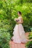 Porträt einer schönen Braut im Park Stockbilder