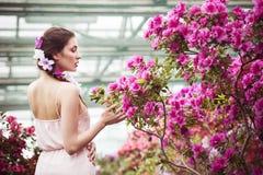 Porträt einer schönen Brunettefrau im rosa Kleid und bunte bilden draußen im Azaleengarten Stockfotografie