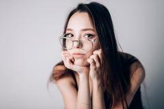 Porträt einer schönen ernsten Frau mit Gläsern auf weißem Hintergrund stockfotografie