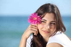 Porträt einer schönen Frau auf dem Strand mit einer rosa Blume Lizenzfreie Stockfotos