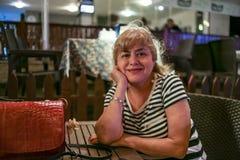 Porträt einer schönen Frau von mittlerem Alter mit einer schönen Zahl und große Brüste in einem schönen Sommer kleiden das Sitzen lizenzfreies stockfoto