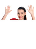 Porträt einer schönen glücklichen Frau, die ihre Hände anhebt. Hinter einem weißen leeren Plakat. Stockfoto