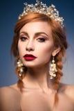 Porträt einer schönen Ingwerfrau mit Krone und den roten Lippen im Bild der Braut stockfoto