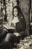 Porträt einer schönen Jugendlichen, die ein Buch in den Vorderteilen liest Lizenzfreie Stockfotografie