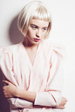 Porträt einer schönen jungen blonden Frau mit dem kurzen Haar im Studio auf einem weißen Hintergrund Stockfotografie