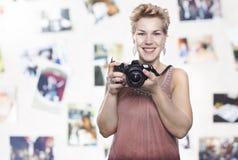 Porträt einer schönen jungen blonden Frau mit einer Kamera Lizenzfreie Stockfotografie