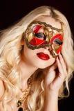 Porträt einer schönen jungen blonden Frau mit Theatermaske auf seinem Gesicht auf einem dunklen Hintergrund Stockbild