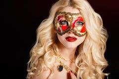 Porträt einer schönen jungen blonden Frau mit Theatermaske auf seinem Gesicht auf einem dunklen Hintergrund Stockfotografie