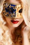 Porträt einer schönen jungen blonden Frau mit Theatermaske auf seinem Gesicht auf einem dunklen Hintergrund Lizenzfreie Stockfotos
