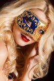 Porträt einer schönen jungen blonden Frau mit Theatermaske auf seinem Gesicht auf einem dunklen Hintergrund Stockfotos