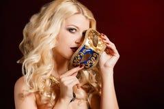 Porträt einer schönen jungen blonden Frau mit Theatermaske auf seinem Gesicht auf einem dunklen Hintergrund Lizenzfreies Stockfoto