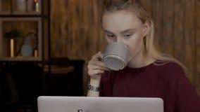 Porträt einer schönen jungen Blondine, die Kaffee hinter einem Laptop trinkt stock video