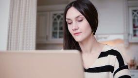 Porträt einer schönen jungen Brunettefrau benutzt Laptop in einem hellen Speisen Stockbilder