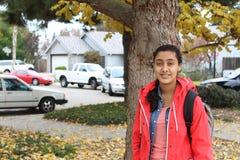 Porträt einer schönen jungen ethnischen Studentin mit einem Rucksack beim Gehen in den Herbstpark Lizenzfreie Stockbilder