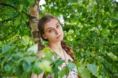 Porträt einer schönen jungen Frau auf einem Hintergrund des grünen Laubs Lizenzfreie Stockbilder