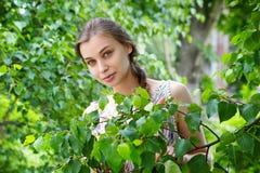 Porträt einer schönen jungen Frau auf einem Hintergrund des grünen Laubs Stockfotos