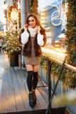 Porträt einer schönen jungen Frau, die auf der Straße nahe dem elegant verzierten Weihnachtsfenster aufwirft, festliche Stimmung stockfoto