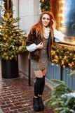Porträt einer schönen jungen Frau, die auf der Straße nahe dem elegant verzierten Weihnachtsfenster aufwirft, festliche Stimmung stockfotos