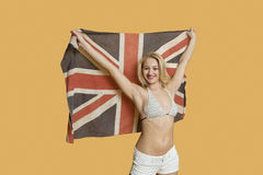 Porträt einer schönen jungen Frau, die britische Flagge mit den Armen hält, hob über farbigen Hintergrund an Stockbild