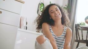 Porträt einer schönen jungen Frau, die an der Kamera in einer Küche lächelt stock footage
