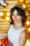 Porträt einer schönen jungen Frau, die ein Geschenk für neues Jahr und Weihnachten hält stockfoto