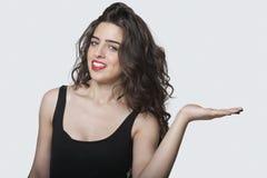 Porträt einer schönen jungen Frau, die ihre Palme heraus über grauem Hintergrund hält Stockbild
