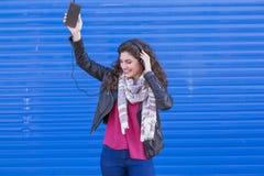 Porträt einer schönen jungen Frau, die Musik auf ihrem MO hört Stockfoto