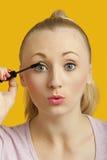 Porträt einer schönen jungen Frau, die Wimperntusche über gelbem Hintergrund anwendet Lizenzfreie Stockbilder