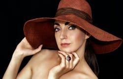 Porträt einer schönen jungen Frau in einem Hut auf einem schwarzen Hintergrund lizenzfreie stockfotos