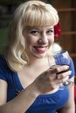 Schöne junge Frau mit dem blonden Haar ein Glas Wein trinkend Stockbild