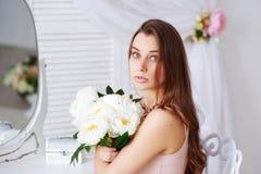 Porträt einer schönen jungen Frau mit einem Blumenstrauß Stockfotografie