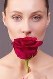 Porträt einer schönen jungen Frau mit einer Rose Lizenzfreie Stockbilder