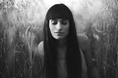 Porträt einer schönen jungen Frau mit geschlossenen Augen auf Feld. stockfotografie