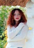 Porträt einer schönen, jungen Frau n eine weiße gestrickte Strickjacke Um das alte Haus mit mit Stroh gedecktem braunem Dach lizenzfreie stockfotografie