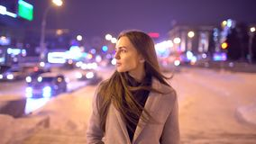 Porträt einer schönen jungen Frau nachts in der Stadt Attraktives Mädchen der Zeitlupe, das zur Kamera schaut Unscharfe Nacht stock video