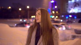 Porträt einer schönen jungen Frau nachts in der Stadt Attraktives Mädchen der Zeitlupe, das zur Kamera schaut Unscharfe Nacht stock footage