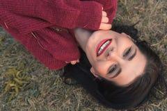 Porträt einer schönen jungen kaukasischen Frau, die den tragenden Strickpullover der Kamera, liegend auf dem Gras lächelt und bet stockfoto