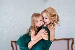 Porträt einer schönen jungen Mutter mit einer netten blonden Tochter, die im weißen Innenraum sitzt, kleidete im eleganten Grün a stockfoto