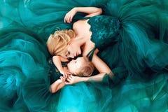Porträt einer schönen jungen Mutter mit einer netten blonden Tochter kleidete in den eleganten grünen Kleidern an lizenzfreie stockbilder