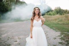 Porträt einer schönen jungen sexy Mädchenbraut mit Blumen in ihrem Haarblick attraktiv in einem weißen Kleid lizenzfreie stockfotos