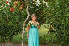 Porträt einer schönen kaukasischen Frau von mittlerem Alter mit einer schönen Zahl und große Brüste in einem schönen Sommer kleid stockfotos