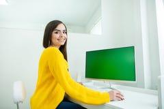 Porträt einer schönen lächelnden Frau, arbeitend am Computer mit grünem Schirm, in einer Büroumwelt stockfotografie