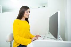 Porträt einer schönen lächelnden Frau, die an ihrem Schreibtisch in einer Büroumwelt arbeitet lizenzfreie stockfotos