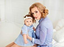 Porträt einer schönen Mutter blond und des Babys des kleinen Mädchens mit b Lizenzfreies Stockfoto
