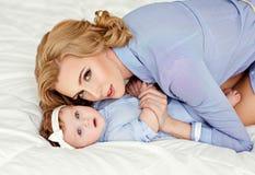 Porträt einer schönen Mutter blond und des Babys des kleinen Mädchens mit b Lizenzfreie Stockfotografie