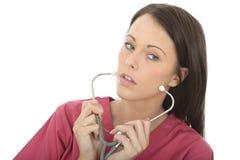 Porträt einer schönen professionellen ernsten jungen Ärztin Putting On ein Stethoskop Stockfotografie